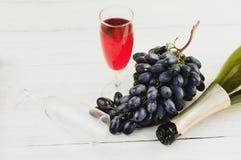 Пук свежих зрелых голубых виноградин около прозрачное и хрупкое стеклянного вполне вина и одного раскрыл бутылку около пустого ст Стоковые Фото