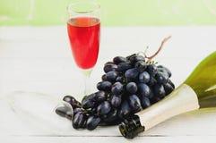 Пук свежих зрелых голубых виноградин около прозрачное и хрупкое стеклянного вполне вина и одного раскрыл бутылку около пустого ст Стоковые Изображения RF