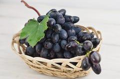 Пук свежих зрелых голубых виноградин с зелеными лист в плетеной корзине на старых деревянных белых планках стоковые изображения