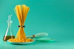 Пук спагетти стоя чистосердечный на яркой покрашенной предпосылке окруженной яйцами, оливковым маслом и варить цыпленка стоковое изображение
