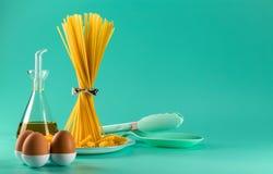 Пук спагетти стоя чистосердечный на яркой покрашенной предпосылке окруженной яйцами, оливковым маслом и варить цыпленка стоковое фото