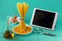 Пук спагетти стоя чистосердечный на яркой покрашенной предпосылке окруженной планшетом, яйцами цыпленка, прованскими стоковые фотографии rf