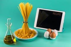 Пук спагетти стоя чистосердечный на яркой покрашенной предпосылке окруженной планшетом, яйцами цыпленка, прованскими стоковое изображение