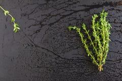 Пук травы тимиана на черной каменной предпосылке, взгляд сверху Использованный как flavoring в варить и также в ароматерапии стоковые фотографии rf