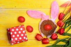 Пук цветков около яичек в гнезде с ушами зайчика Стоковое Изображение