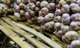 Пук чеснока на естественной бамбуковой полке Стоковое Фото