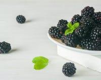 Пук dewberries на белой плите Светлая предпосылка Светлое тоновое изображение Стоковое Изображение