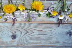 Пук fieldflowers, маргариток, лютиков, Pentecostal цветков, одуванчиков на предпосылке oldwooden с пустым космосом экземпляра Стоковое Изображение RF