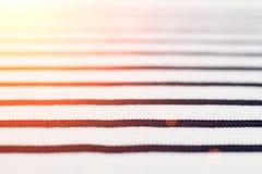 Пуловер с черными нашивками, предпосылка шерстей белый текстуры, тонизировал солнечный свет Стоковое фото RF