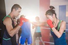 Пунш молодого женского боксера практикуя с мужчиной Стоковое Изображение