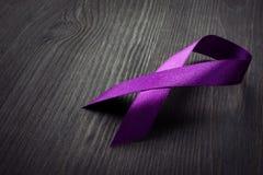 Пурпурная лента осведомленности на столе Поджелудочный рак стоковое изображение