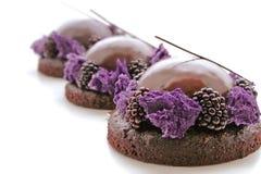 3 пурпурных десерта шоколада с сияющей поливой зеркала и свежими ежевиками стоковые фотографии rf