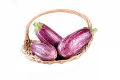 Пурпуровые aubergines в корзине сторновки Стоковое Изображение RF
