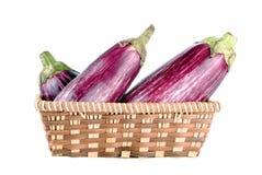 Пурпуровые aubergines в корзине сторновки Стоковая Фотография RF
