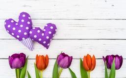 Пурпур 2 поставил точки сердца с красивыми цветками тюльпанов на белой предпосылке деревянного стола с космосом экземпляра Стоковое фото RF