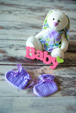 Пурпур связал носки младенца с надписью ребенка и зайца игрушки на деревянной предпосылке Стоковое Фото