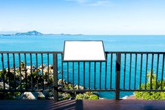Пустая афиша рекламы на стальной загородке над спокойным голубым морем стоковое изображение rf