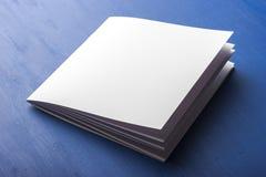 Пустая белая бумага для примечаний, тетрадь, дневник, буклет, организатор на голубой предпосылке Стоковое Изображение RF