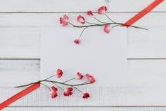 Пустая белая карточка украшает с красными бумажными цветками и красной лентой Стоковые Фотографии RF