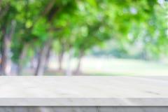 Пустая белая мраморная таблица над предпосылкой природного парка зеленого цвета нерезкости, стоковая фотография rf