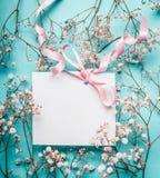Пустая белая поздравительная открытка с розовой лентой на маленьких белых цветках на предпосылке сини бирюзы Стоковое Изображение RF