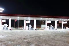 Пустая бензозаправочная колонка с освещением на темной ноче зимы Стоковое фото RF