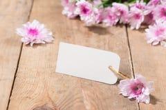 Пустая белая бумага бирки с цветом цветет на деревянной предпосылке T Стоковое фото RF
