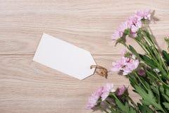 Пустая белая бумага бирки с цветом цветет на деревянной предпосылке T Стоковое Изображение