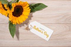 Пустая белая бумага бирки с цветом цветет на деревянной предпосылке T Стоковые Фото