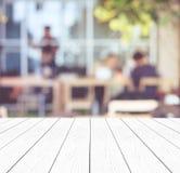 Пустая белая деревянная перспектива, столешница, над группой в составе нерезкости peopl Стоковые Изображения RF