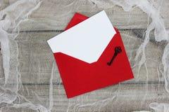 Пустая белая карточка примечания в конверте с железным ключом на затрапезной предпосылке Стоковое Изображение
