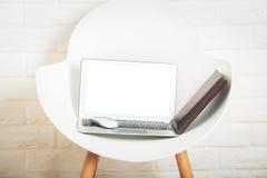 Пустая белая компьтер-книжка на стуле Стоковые Фото