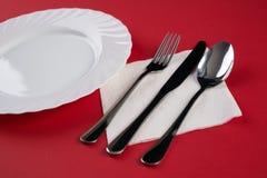 Пустая белая плита обедающего при серебряный Tablespoon вилки и десерта, изолированный на красной предпосылке скатерти с космосом Стоковые Фото