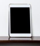 Пустая белая таблетка на деревянной полке с пустым экраном стоковая фотография