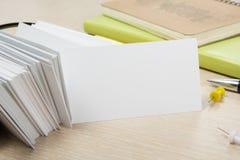 пустая белизна визитной карточки Стол таблицы офиса с комплектом красочных поставек, чашкой, ручкой, карандашами, цветком, примеч Стоковое Фото