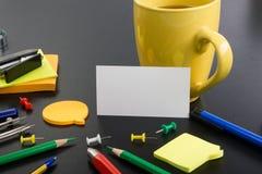 пустая белизна визитной карточки Стол таблицы офиса с комплектом красочных поставек, чашкой, ручкой, карандашами, цветком, примеч Стоковые Фото