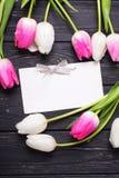 Пустая бирка и розовые и белые тюльпаны цветут на винтажной черноте Стоковое Изображение