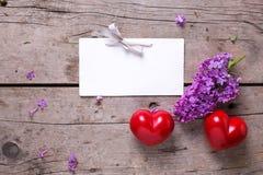 Пустая бирка, 2 красных сердца и свежей фиолетовой сирень цветут на времени Стоковое Изображение RF