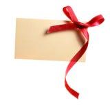 Пустая бирка подарка связанная с смычком красной ленты сатинировки. Изолированный на белизне Стоковое Изображение