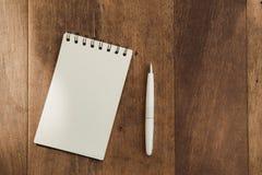 Пустая бумага тетради для текста с белой ручкой на деревянном столе Стоковое Изображение RF