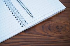 Пустая бумага тетради с серебряной ручкой на предпосылке деревянного стола Стоковые Фото