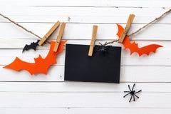 Пустая бумажная карточка висит на зажимках для белья с декоративными летучими мышами Стоковые Фото