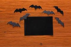 Пустая бумажная карточка с декоративными летучими мышами на оранжевом деревянном backgroun Стоковые Изображения RF