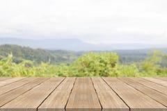 Пустая верхняя часть деревянного стола на запачканной предпосылке на горе Стоковое Фото