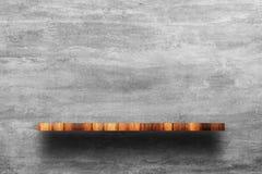 Пустая верхняя часть деревянной полки с чуть-чуть бетонной стеной стоковое изображение