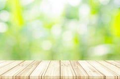 Пустая верхняя часть деревянного стола с запачканной зеленой естественной предпосылкой Стоковое Изображение RF