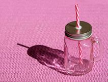 Пустая винтажная кружка с розовыми соломой и крышкой на розовой предпосылке стоковое фото