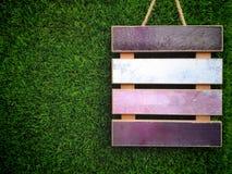 Пустая деревянная доска ярлыка на искусственной предпосылке зеленой травы Стоковые Изображения
