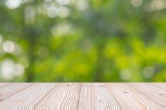 Пустая деревянная таблица на зеленой естественной предпосылке в саде на открытом воздухе Глумитесь вверх для ваших дисплея или мо стоковое фото rf