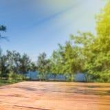 Пустая деревянная таблица палубы с предпосылкой нерезкости парка стоковое фото